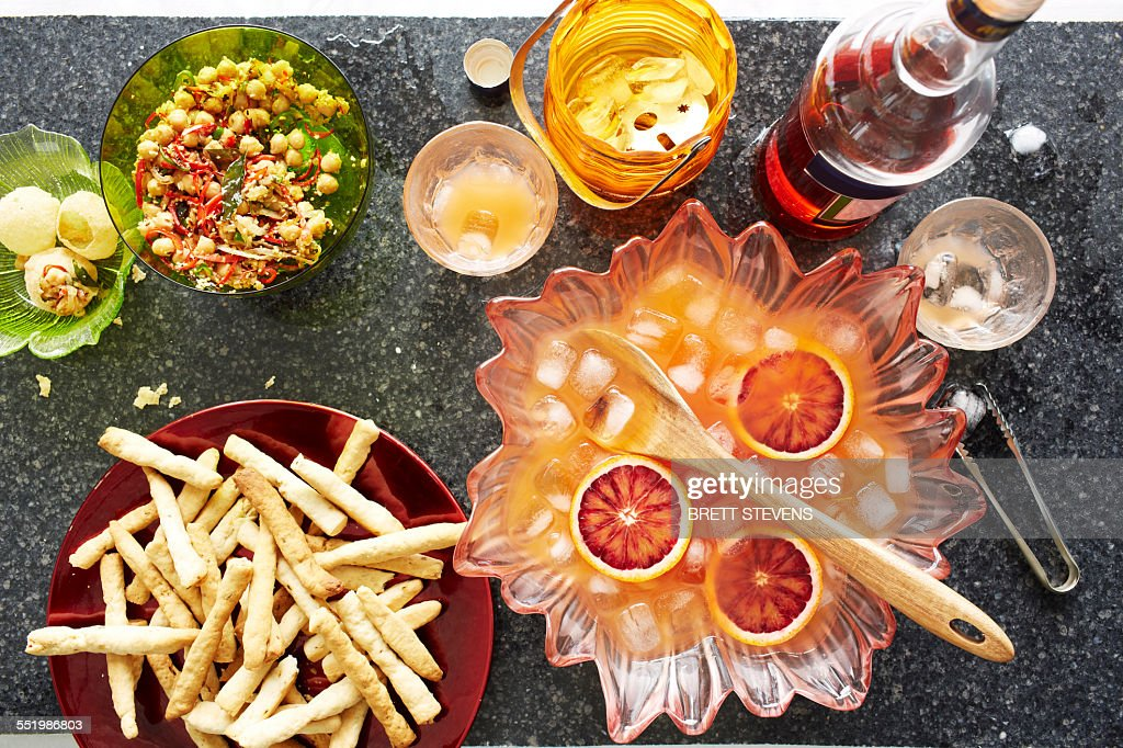 Still life of punch cocktail bowl with crisps and snacks