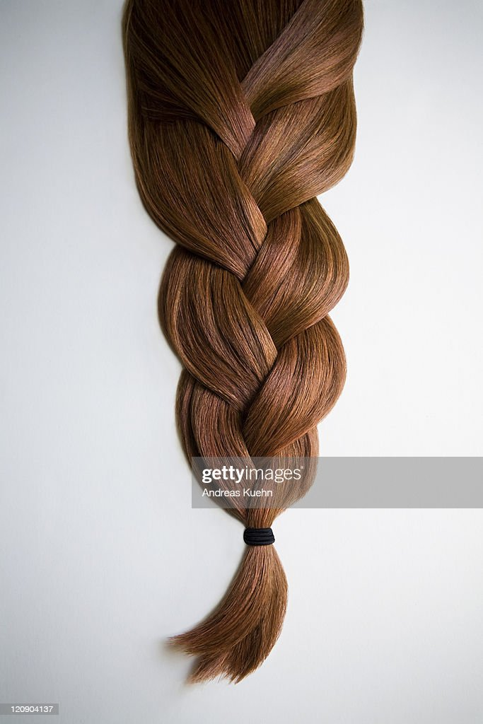 Still life of red haired braid on white background