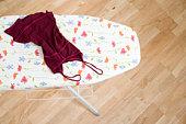 still life of red summer dress on ironing board