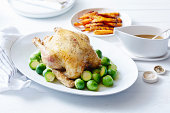 Still life of roast chicken with brussel sprouts and carrots