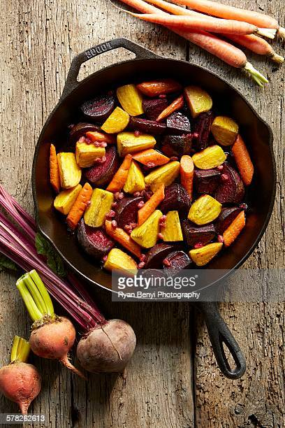 Still life of roasted golden and red beets with carrots in pan