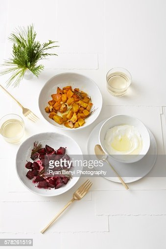 Still life of roasted golden and red beets with pine, served with olive oil yogurt