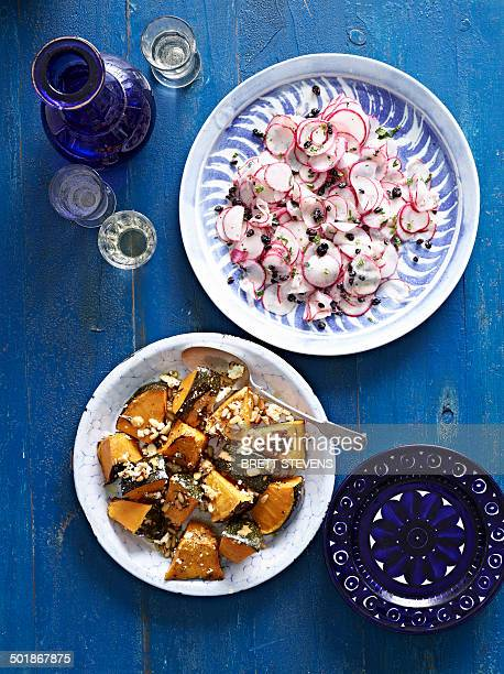 Still life of roasted pumpkin with feta cheese and sliced radish
