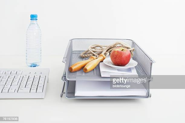 still life of rope and apple in tray on office desk