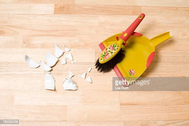still life of shards broom and dustpan on floor