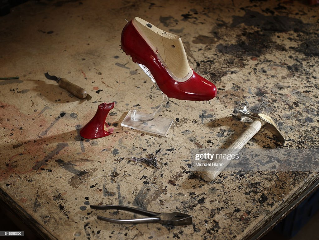 still life of shoes with hammer and tools on bench : Stock Photo