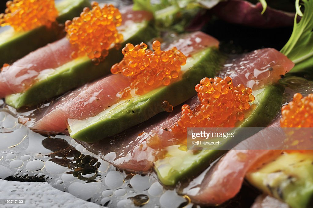 Still life of sliced avocado with fish and fish roe