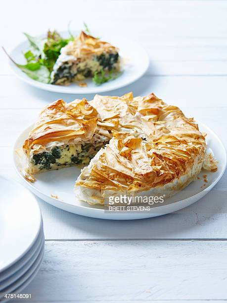 Still life of spanakopita with sliced portion