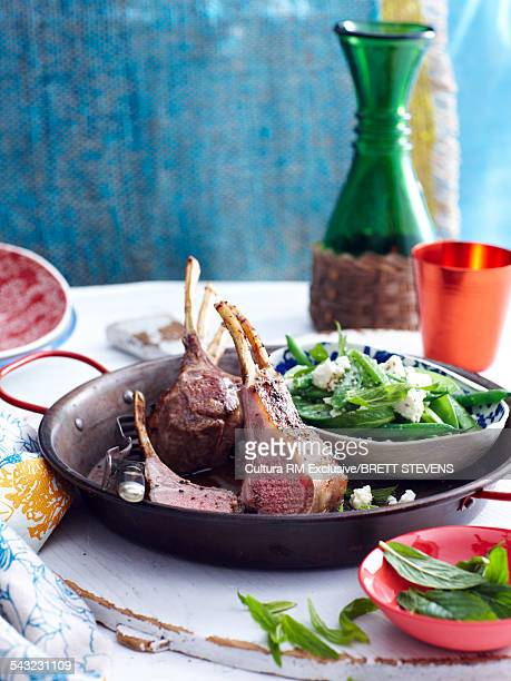 Still life of spring lamb chops with mint peas and feta cheese