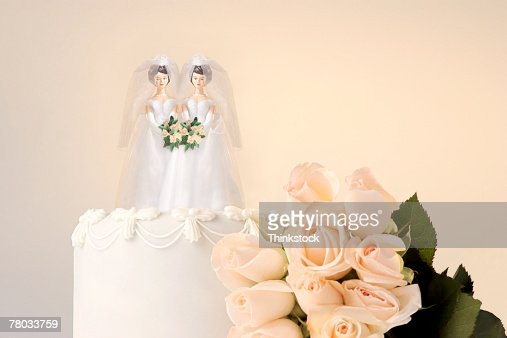 Still life of the top of a wedding cake with two miniature brides cake topper and roses at the side