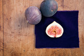 Still life of three figs, one sliced in half on purple cloth