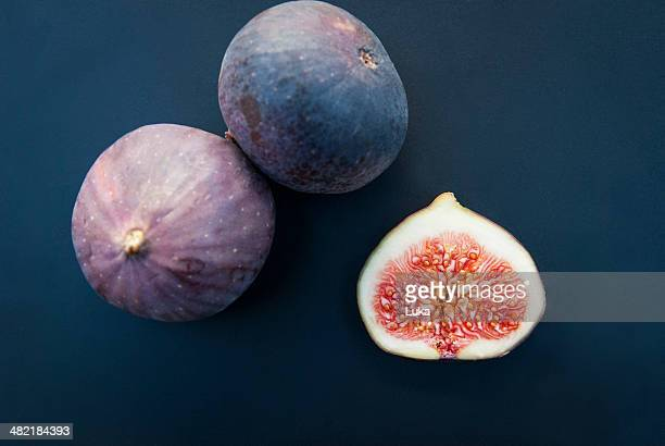 Still life of three figs, one sliced in half