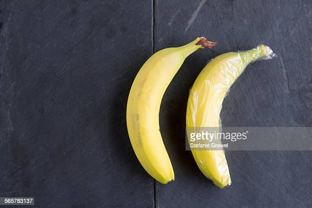 Still life of two bananas - one wrapped in plastic wrap