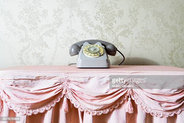 Still life of vintage telephone on frilly tablecloth
