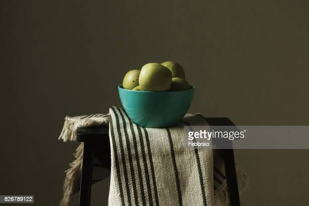 Still life of yellow apples in a blue bowl on striped tablecloth