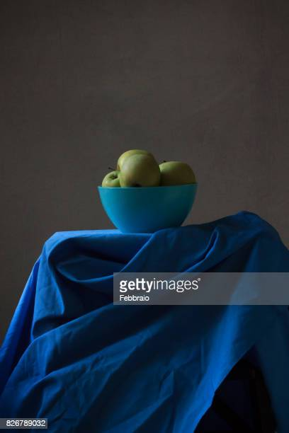 Still life of yellow apples in a blue bowl with window light