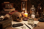 Alchemy still life with skull and burning candle.
