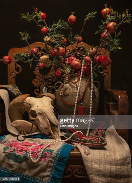 Still life photograph with goat skull, vase with rose hip on branches and jewelry