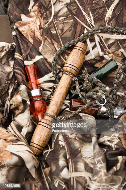 Still life shot of bird calls against camouflage clothing.