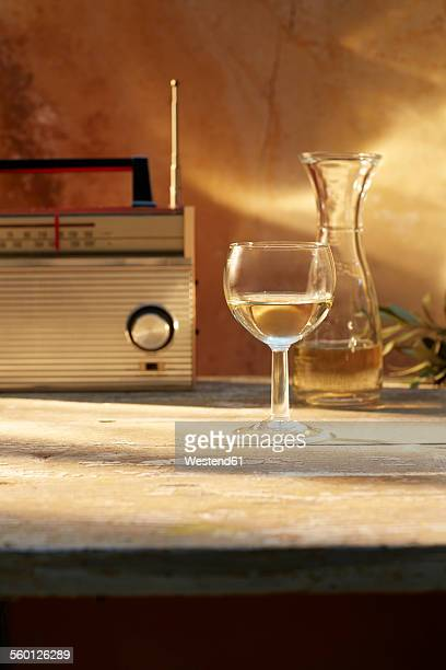 Still life with glass and carafe of white wine and an old radio