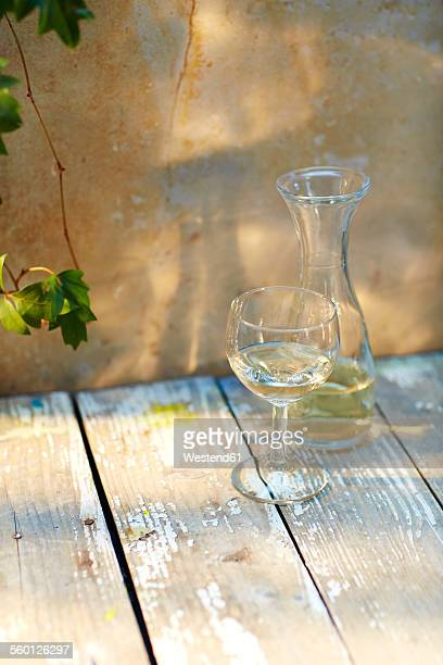 Still life with glass and carafe of white wine and wine leaves