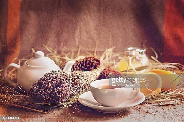 Still life with lemons, teapot, teacup, herbs, lemons and honey