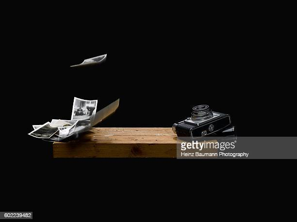 Still life with old camera and flying photographs on black background