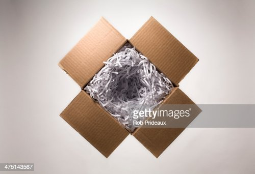 Still life with open cardboard box and shredded paper