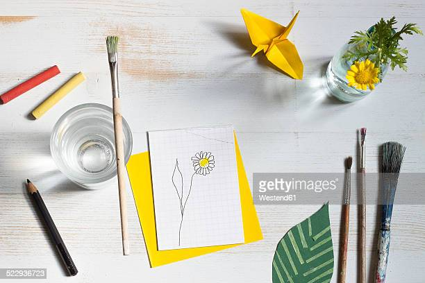 Still life with paintbrush, flower and bricolage