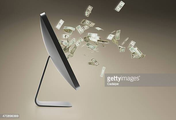 Still life with personal computer and floating dollar bills