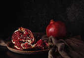 Still life with red juicy pomegranates over dark background. Organic Bio fruits