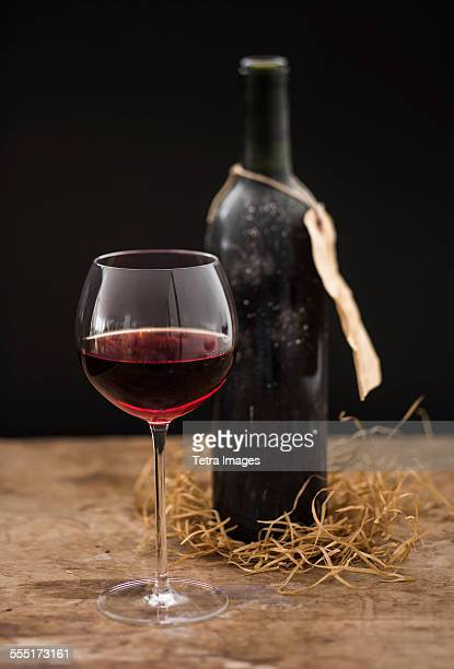 Still life with red wine glass and bottle on wooden table, studio shot