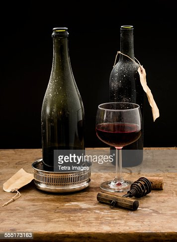 Still life with red wine glass and bottles on wooden table for Red glass wine bottles suppliers