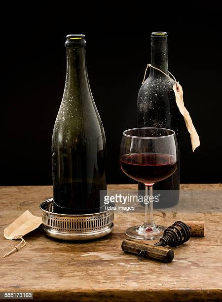 Still life with red wine glass and bottles on wooden table, studio shot