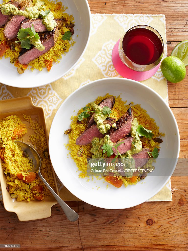 Still life with sliced fragrant lamb and nutty couscous : Stock Photo
