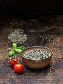 Still life with vine tomatoes, fresh basil and bowl of puy lentils