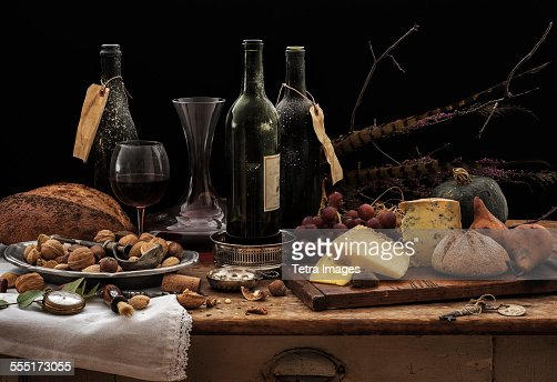 Still life with wine bottles, selection of cheese, bread and nuts on wooden table, studio shot : Stock Photo