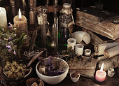Vintage still life with witch books, scrolls, herb and candle. Old pharmacy, esoteric or alternative medicine concept. Black magic and occult objects, alchemist ritual in medieval laboratory