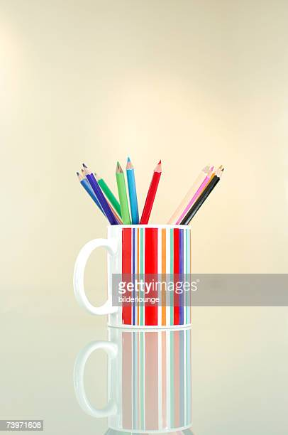still of coloured pencils in striped cup