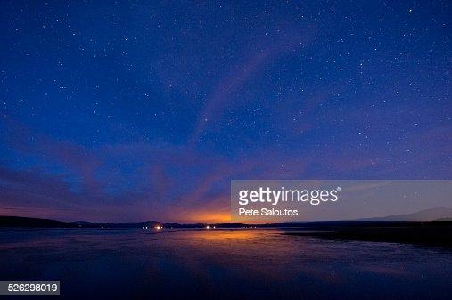 Still rural lake under starry night sky