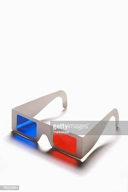 Still-life of a pair of 3D glasses lying on white surface.