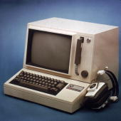 Stilllife of a small RCA computer with the monitor and keyboard in one unit alongside a set of headphones 1970s