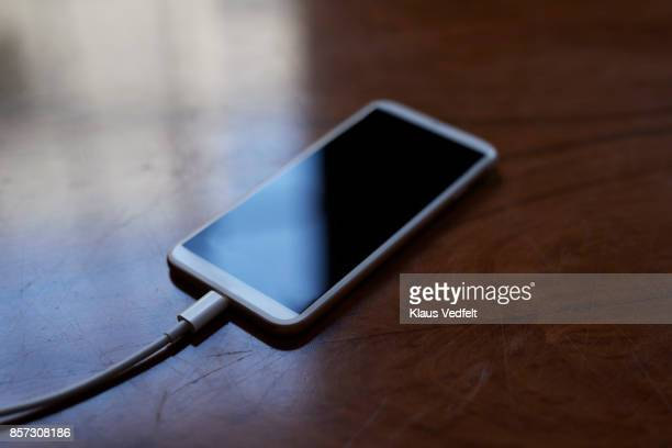 Still-life of smartphone charging on wooden table