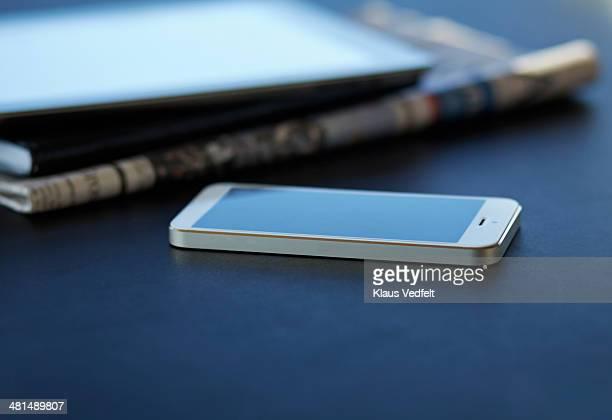 Still-life of smartphone, tablet & newspaper
