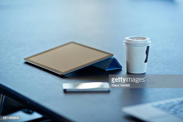 Still-life of tablet, to-go coffee & phone