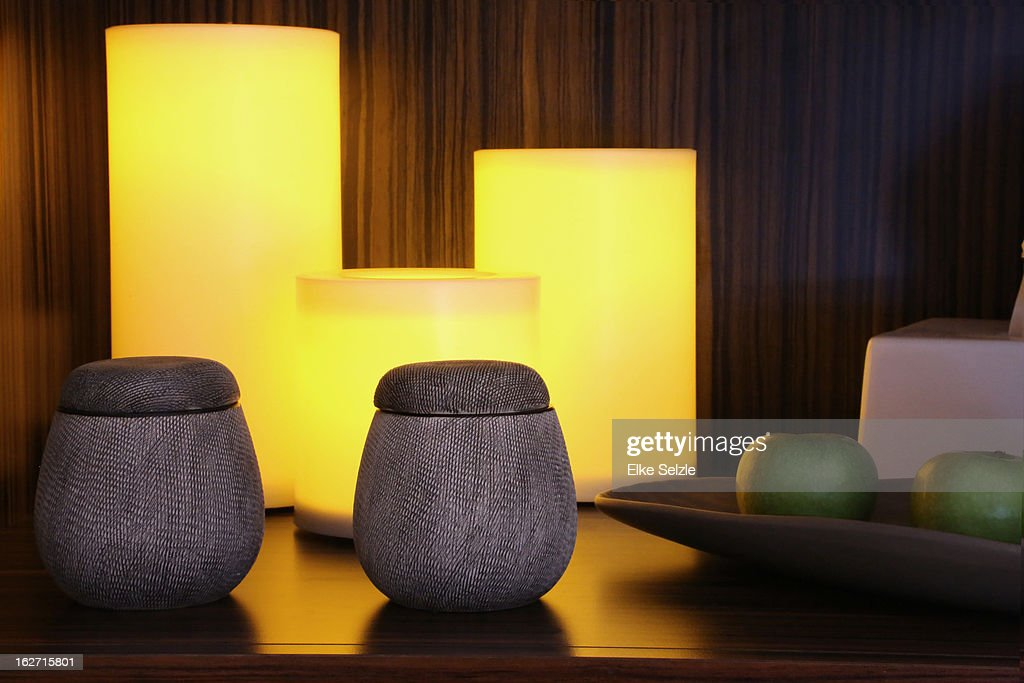 Still-life of vessels,candles and apples on shelf : Stock Photo