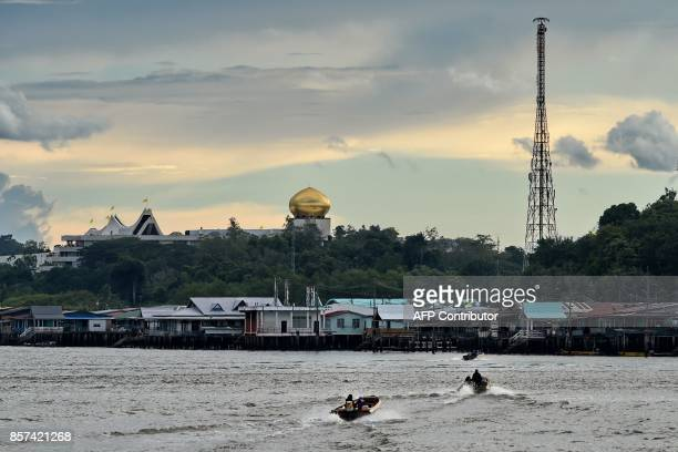 Stilt houses on Kampung Ayer are seen past the Istana Nurul Iman palace in Bandar Seri Begawan on October 4 2017 Brunei will mark its Sultan's...