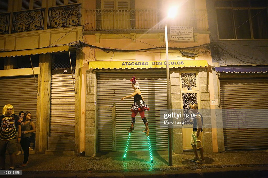 A stilt-walker strides towards revelers during the My Light is LED 'bloco' pre-Carnival street parade on February 12, 2015 in Rio de Janeiro, Brazil. Carnival runs this year February 13-17.
