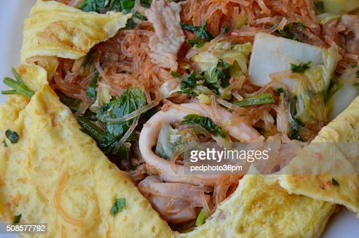 stir fried sukiyaki with seafood wrapped in egg on dish : Stock Photo