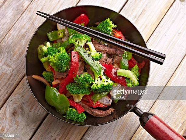 Stir fried vegetables in a mini wok with chopsticks, on wood
